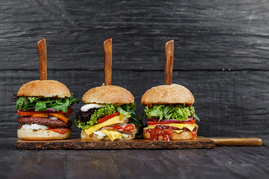 Delicious fresh hamburgers served on wooden plank with knife
