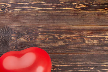 Balloon on wooden background, cropped image. Red heart shaped balloon for party and copy space.