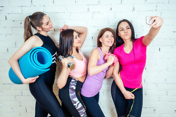four beautiful and young women girlfriends are photographed selfie on the phone in sportswear in the gym.