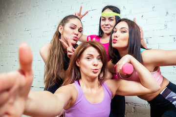 four beautiful and young women girlfriends are photographed selfie on the phone in sportswear in the gym. group portrait of a woman selfie having fun.