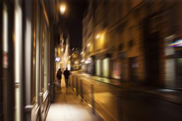 Blurry motion image of people walking on street at night in Paris.