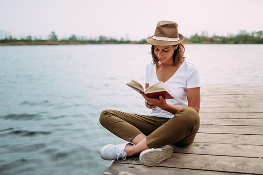 Portrait of a girl reading a book while sitting on a small wooden wharf.