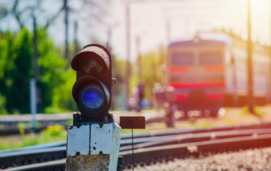 Blue shunting light with a train on the background at the sunset