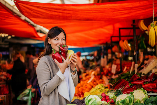 Wonderful smell of fresh vegetables. Beautiful woman at farmers market.