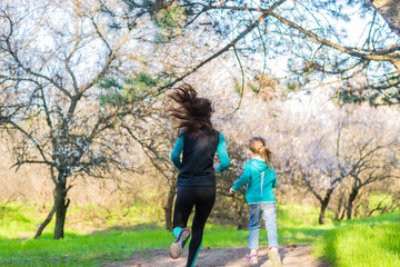 Morning jogging, mom and daughter are running along the forest trail, free space.
