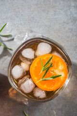Glass with ice cold tea beverage and rosemary garnish