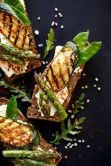Vegetarian sandwich. Wholemeal bread sandwiches with feta cheese, grilled zucchini, green asparagus, sugar peas, olive oil and herbs on a dark background, top view. Healthy and delicious food