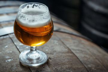 Snifter beer glass on a wooden barrel
