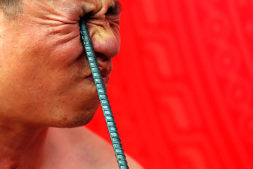 Ngo Chien Thuat, a traditional health worker, bends a metal pole by pressing it into his eye as he performs during a showcase of the traditional Thien Mon Dao kung fu at Du Xa Thuong village