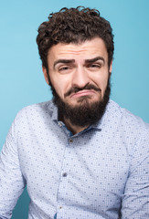 Studio portrait of unhappy young man with a grimace on his face. Beard, mustache and a light shirt