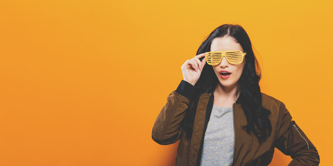 Fashionable woman in a bomber jacket on a golden yellow background