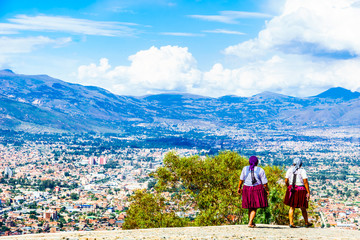 Indigenous people in fron of the cityscape of Cochabamba in Bolivia