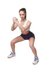 Full length teen girl smiling doing fitness exercises squat , isolated on white background