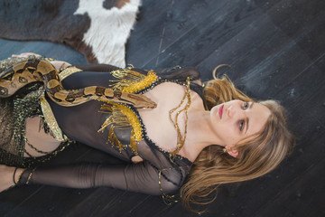 Young blonde woman lying on the floor with python on her body in a studio