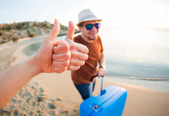 Young man arriving at the resort and standing on the beach while showing thumbs up