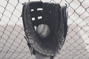 American sport of baseball shows closeup of ball in black and white with glove.  Dugout fence in background