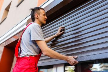 Man installing roller shutter on window