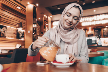beautiful Arab girl with a headscarf on her head dines in a cozy oriental cafe, drinks tea and smiles