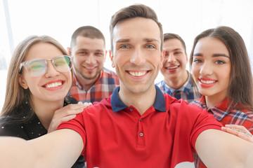 Happy friends taking selfie indoors