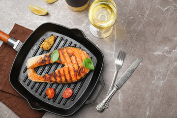 Frying pan with tasty salmon steak and wine on grey background