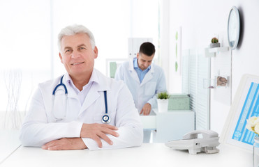 Senior male doctor working at reception desk in hospital