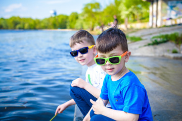 Children playing outdoors in nature: sitting on lake or river shore touching sand in clear water on warm summer or spring day.