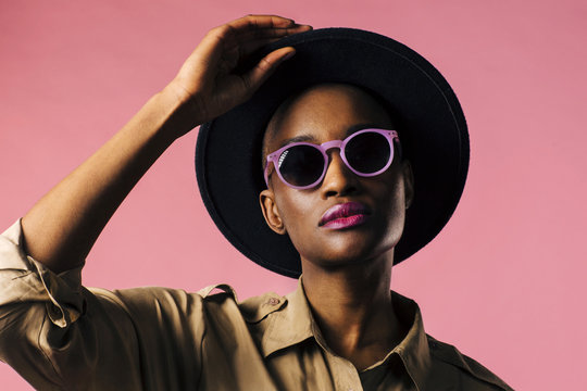A fashion portrait of a young woman with purple sunglasses and black hat, isolated on pink studio background