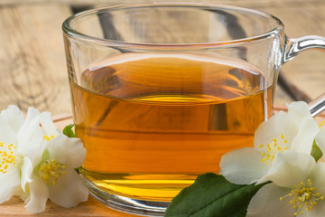 green tea and jasmine flowers, tea with jasmine, tea mug on a wooden board