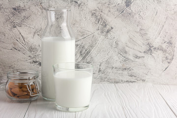 Bottle of almond milk with glass and almonds in jar on rustic white wooden table. Copy space for text and logo