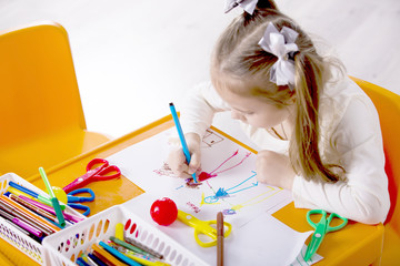 Little girl draws a greeting card to mum. Many multi-colored pencils and markers on the orange table in the nursery