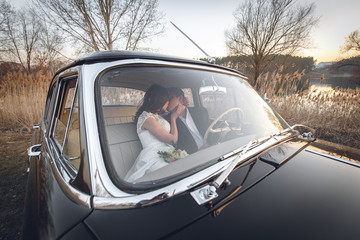 Young wedding couple sitting smiling inside retro car and are kissing each other. just married embrace is hugging inside car. bride hugging groom who is driving the car. Wedding with retro car.