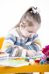 Little girl draws a greeting card to mum. Many multi-colored pencils on the orange table in the nursery