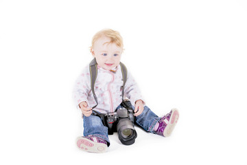 Little curly girl with a big camera on white background