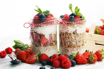 Glass jar of homemade granola with yogurt and fresh berries