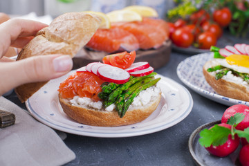 Bread with cheese, radish, salmon and asparagus, in a woman's hand. Different Healthy Eating. Delicious breakfast for the family. Food in the Netherlands