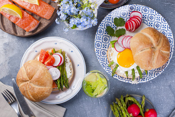 Bread with cheese, egg and asparagus, another bread with salmon and. asparagus. Healthy food. Tasty breakfast. Gray background.
