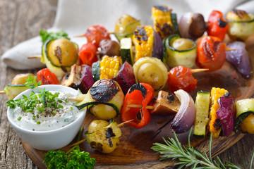 Veggie Gemüse: Bunte  gegrillte Gemüsespieße mit Kräuterdip  - Grilled skewers with mixed vegetables served  on a wooden cutting board with a vegan herb dip