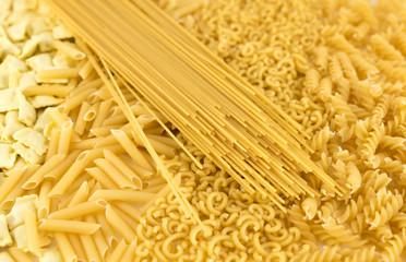 Raw pasta variety background: curls, fideuá, macaroni, pasta stuffed with meat and spaghetti