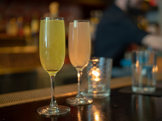 Two wineglasses filled with mimosa drinks with bartender in background