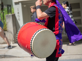 Man playing a wadaiko percussion drum as part of a Japanese parade