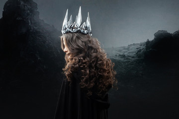 Portrait of a Gothic Princess. Beautiful young brunette woman in metal crown and black cloak.