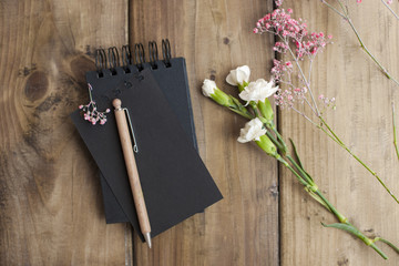 Notepad for notes and flowers. Wooden background. Place for text