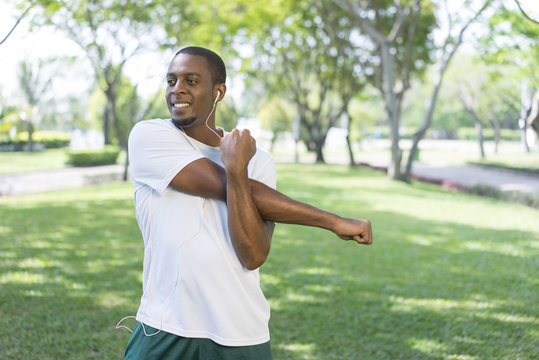 Smiling sporty black man listening to music and doing morning exercises in park. Young Afro American sportsman stretching hand and deltoid muscle. Fitness and street workout concept