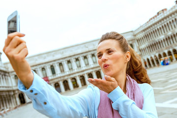 Young woman blowing kiss and making selfie on piazza san marco i