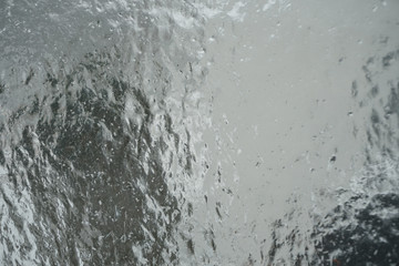 Surface of window after winter storm covered with ice, abstract natual background