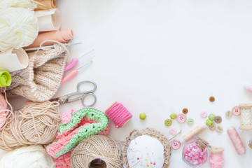 There are many different materials for needlework. Knitting and sewing. A girl / woman knits and drinks cappuccino.