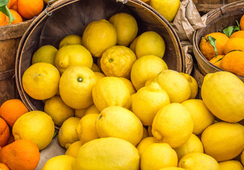 full frame close up of wooden buckets filled with ripe brightly colored lemons and oranges at a farmer's market