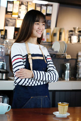 Young asian women barista standing with smiling face in font of a coffee cup at cafe counter background, small business owner, food and drink industry concept