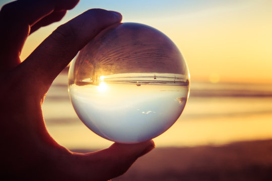 Creative photography Landscape concept with crystal ball or esphere in hand during sunset on beach