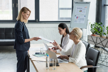 beautiful businesswoman giving documents to colleague at meeting in office